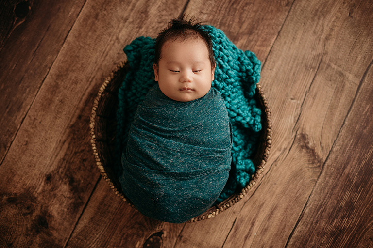 2 month old swaddled baby in basket teal raleigh