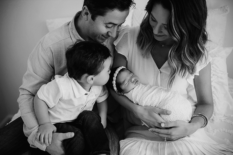 newborn family with big brother kissing sister in Cary